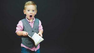 barn med åpen munn leser bok, intelligent unge