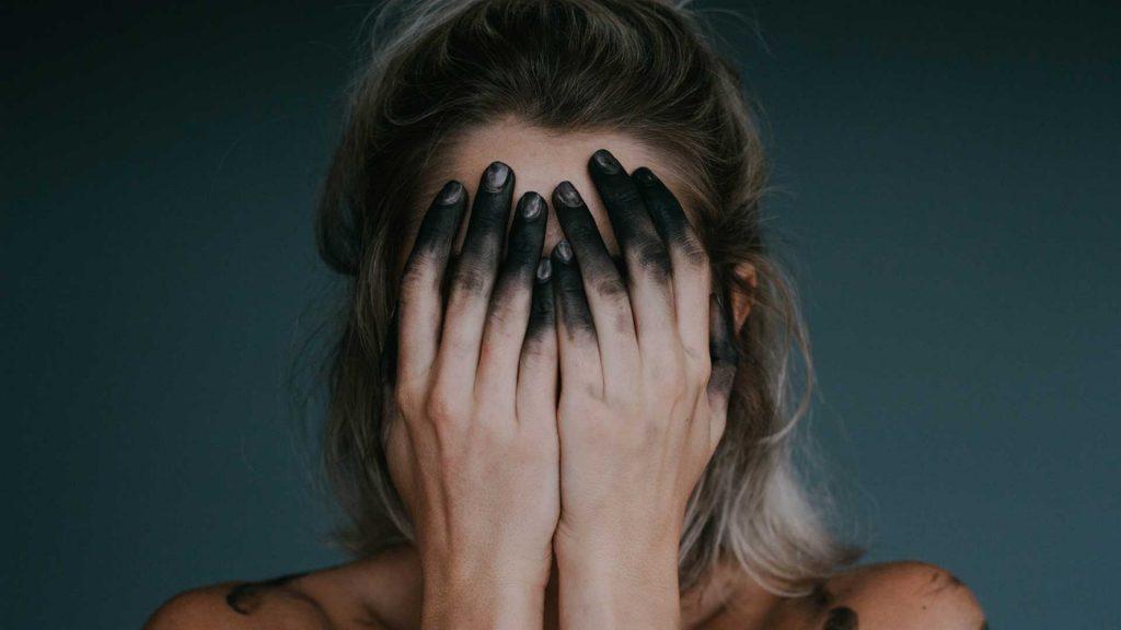 deprimert kvinne med sorte fingre