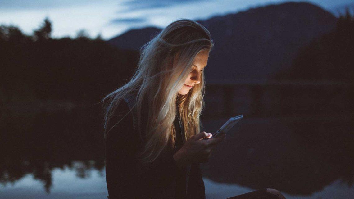 kvinne ser mobiltelefon, blått lys gir søvnvansker