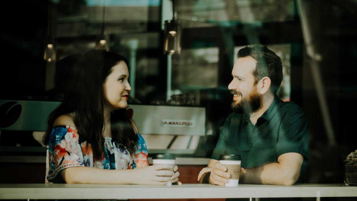 kvinne og mann samtaler over en kaffe